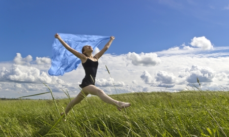 Young ballerina dancing on the nature of the field on the background of blue sky in the hands holding the handkerchief jumps flies photo