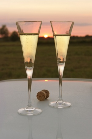 glass two with champagne on the table reflects the sunset photo