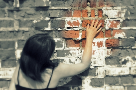 woman pressed against the brick wall and touched her hand photo
