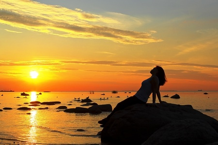 silhouette of the woman beach sea lake at sunset sitting on the stone looks at sun stretching the arms photo