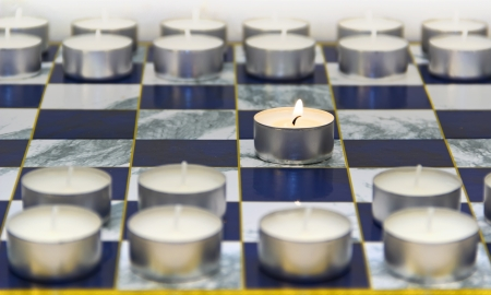 first move: Burning candle chessboard game started first move Stock Photo