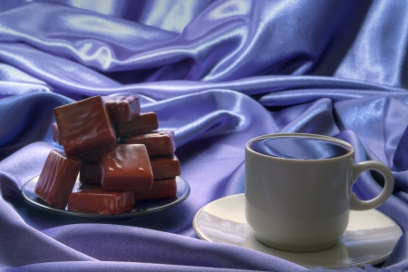 a cup of hot  black coffee with caramel cube photo