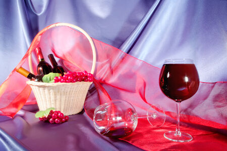 Bottle glass wine grapes wicker basket scarf red blue fabric Stock Photo