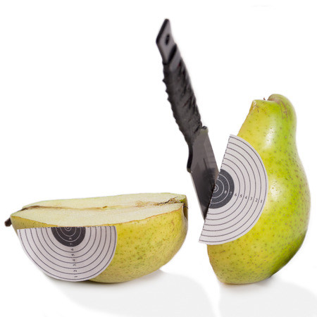 throwing knife: Target ripe pear throwing knife green reflection isolated white background