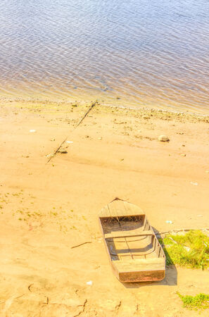 dikes: old boat shore  river sky sand beach Stock Photo