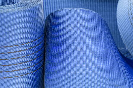 Wide nylon flat rope stitched with thread wound into a roll  background blue