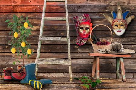 ceramic bottle: Two carnival masks hanging  wall  bottom  wooden bench  wicker basket bottles  wine  grapes straw hat  floor broken bottle staircase two pairs shoes mens womens  lemon tree  ceramic pot