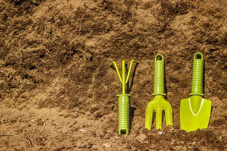 black soil: Garden tools green  background  black soil Stock Photo
