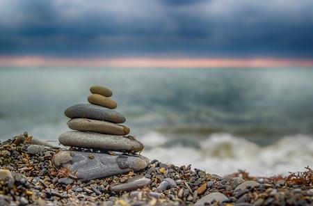 Pyramid  smaller stones on  seashore sunset wave