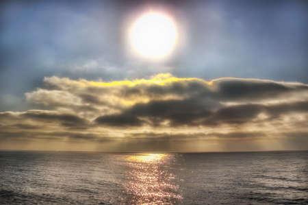 Great sun over  cloudy sea  path light calm center