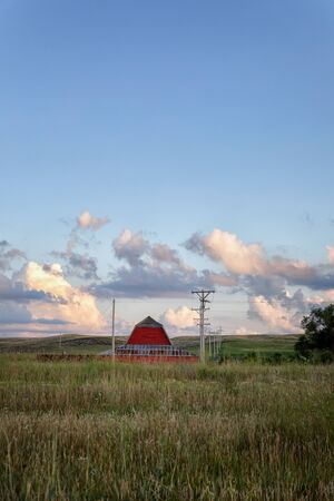 Landscape photo of an abandoned red barn in a grassy field with clouds, powerlines, trees, and haybales in Rural Nebraska