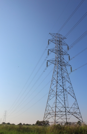 transmission line: Electric high voltage power post in the field Stock Photo