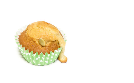 Closeup over the mold paper of homemade banana muffin on white background