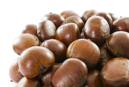 Closeup stack of roasted chestnuts on white background