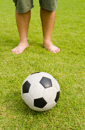Old football on green grass