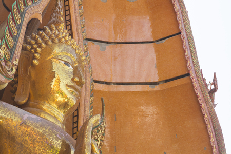 Closeup face of large Buddha covered in golden mosaics of Buddhist Temple.We can call 'Wat Tham Seua'. It right in Kanchanaburi province of Thailand Archivio Fotografico