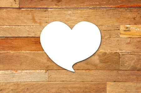 White heart paper on old wood background photo