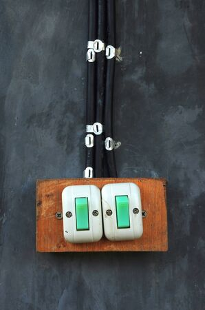 Old switch with black cable on the gray cement wall photo