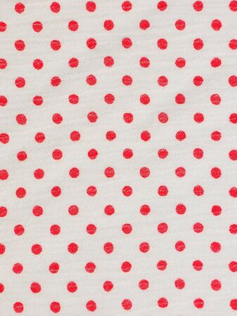 Red ploka dot on white fabric texture background photo