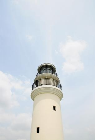 White lighthouse on the blue sky photo
