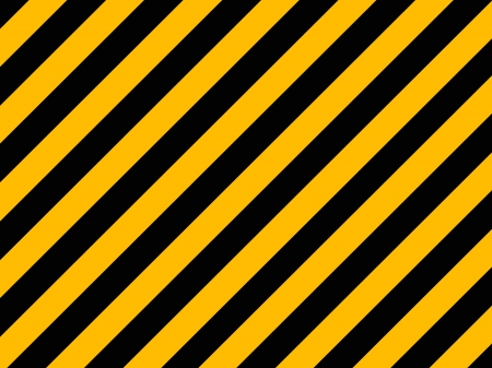 Yellow and black diagonal hazard stripes painted on old brick wall