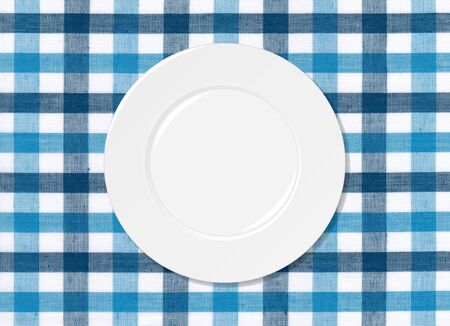 White plate on blue and white tablecloth background photo