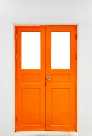 Orange door on white wall photo