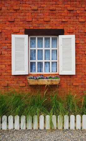 White window on brick wall with green grass and white fench photo
