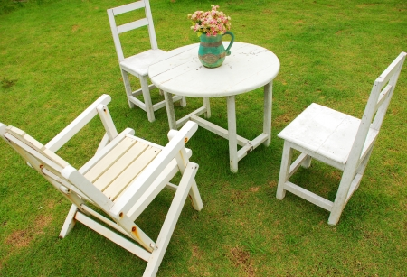 White chairs with round table on green grass photo