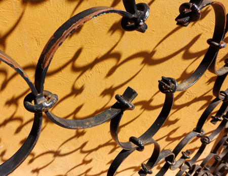 A beautiful iron fence with shadow on the wall background