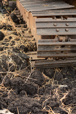 Close up of caterpillar track on black soil with straw background photo