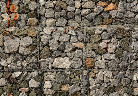 gabion: Stone fence protected by applicable Grids background Stock Photo