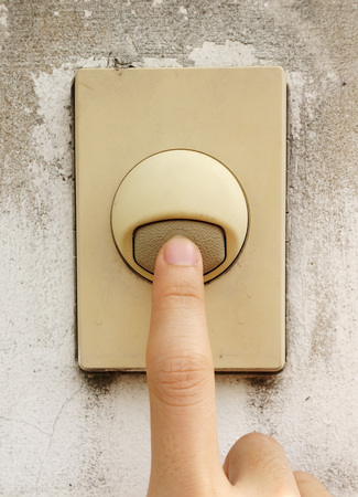 Finger pressing on old door bell switch button Stock Photo
