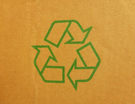 recycle symbol: Green recycle symbol on cardboard background Stock Photo