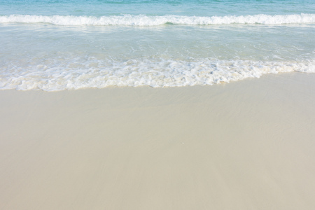 Soft blue ocean wave on sandy beach background