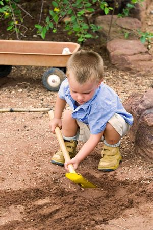 toddler playing in the sand with shovel and cart Stock Photo