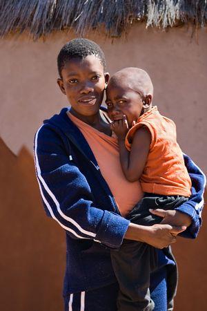 彼の目に涙を浮かべてカラハリ砂漠の過酷な太陽の下で、アフリカの子供の肖像画。ボツワナ、アフリカ。
