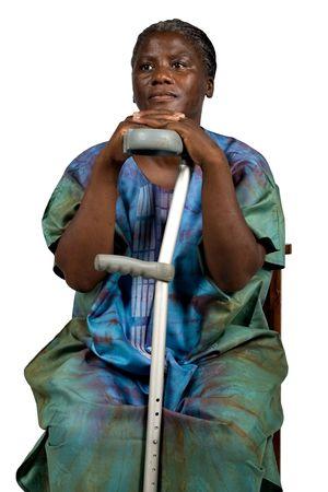 paraplegic: ongeldige oude Afrikaanse vrouw met een kruis, witte haren in traditionele kleding, natuurlijk, geen make-up