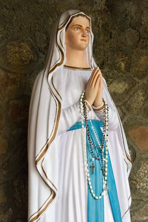 rosary beads: Gypsum statue of virgin Mary with crucifix and rosary praying beads