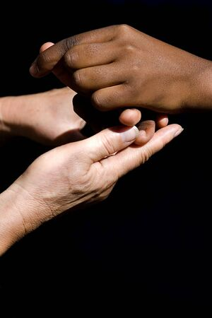 Old Caucasian woman, teacher holding the hands of her African American student.