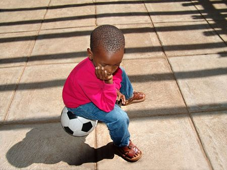 African American child sitting on the ball waiting for his friends at school for a soccer game.                                photo