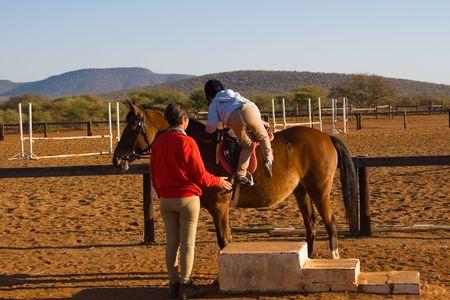 levantandose: Muchacha peque�a que se levanta el caballo, amaestrador al lado de ella, serie de la diversidad de la gente,