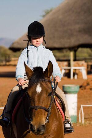 riding helmet: Muchacha peque�a que monta el caballo, serie de la diversidad de la gente, Foto de archivo