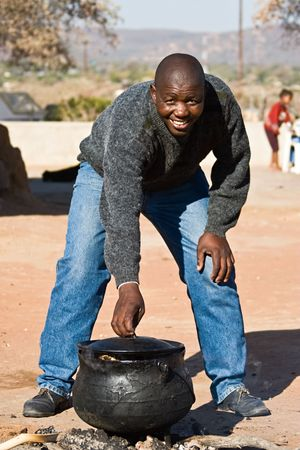 disadvantaged: Three legged pot with traditional African food , setswa, African adult, people diversity series