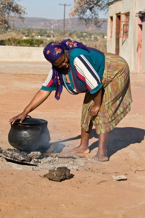 disadvantaged: Three legged pot with traditional African food , setswa, African adult woman , people diversity series