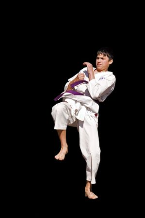 karateka: young karateka training, isolated on black, sport series