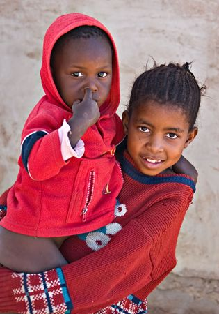 Deprived African children, sister and brother, village near Kalahari desert, people diversity series photo