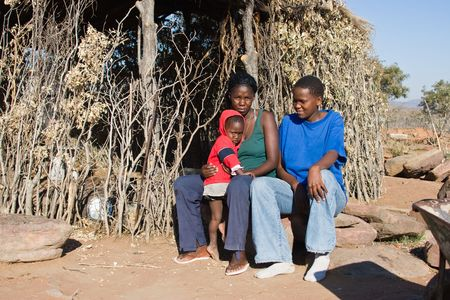 Child, mother and auntie, family portrait, traditional house, Kalahari desert