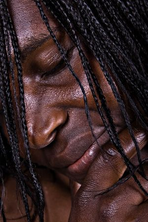 low-key African woman portrait, special light was used to make obvious the wrinkles,  photo