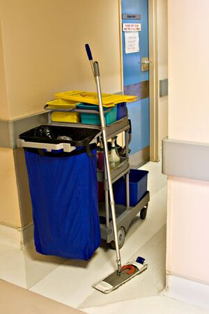 Cleaning instruments, chemicals, garbage bin, in a push trolley, hospital hallway Stock Photo